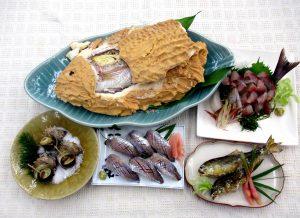 魚屋の店先に並んだ色々な魚介をさばいて料理する講座